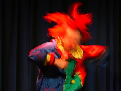 Ein tanzender Clown, in der Bewegung kaum mehr als ein bunter Fleck